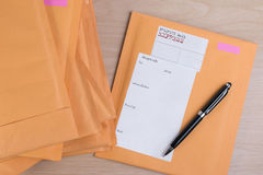 Stack of bubble wrap padded mailing envelopes and pen on white b Stock Image