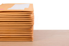 Stack of bubble wrap padded mailing envelopes and pen on white b Stock Photos