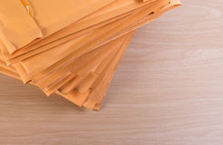 Stack of bubble wrap padded mailing envelopes and pen on white b Royalty Free Stock Photo