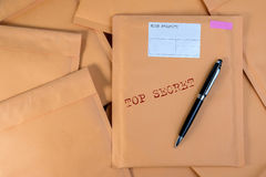 Stack of bubble wrap padded mailing envelopes and pen on white b Royalty Free Stock Image