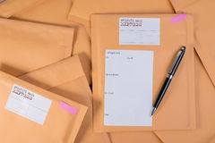 Stack of bubble wrap padded mailing envelopes and pen on white b Stock Photo