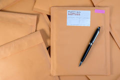 Stack of bubble wrap padded mailing envelopes and pen on white b Royalty Free Stock Images