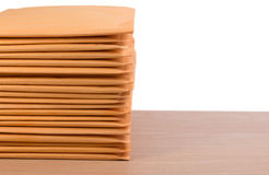 Stack of bubble wrap padded mailing envelopes on white background color over wooden table. Stock Photos