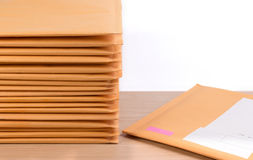 Stack of bubble wrap padded mailing envelopes on white background color over wooden table. Envelope packaging shockproof stack concept Stock Image