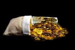 Stack bundles of 100 US dollars banknotes and gold coin in treasure sack on black background stock photos