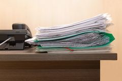 Stack of business documents on wooden office desk.Concept of business,working place,overworking.Paper files is near black. Concept of business,working place stock photo
