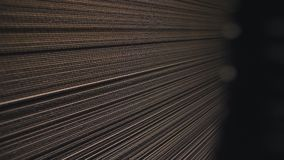 Stack of cardboard paper in dark plant warehouse closeup. Large stack of new brown cardboard paper sheets in dark production plant warehouse closeup stock video