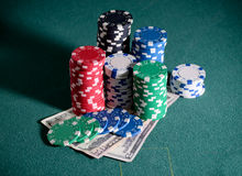 Stack of casino chips and dollar bills on the poker table Stock Photo