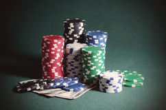 Stack of casino chips and dollar bills on the poker table. Vintage tonned photo Royalty Free Stock Photo