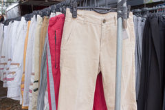 Stack of casual cotton men's trousers. Hanging show at the marketplace Royalty Free Stock Photos