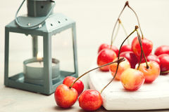 Stack of cherries on white wooden background with lit lantern Stock Image