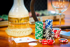 Stack of chips to play poker and two aces Royalty Free Stock Photo