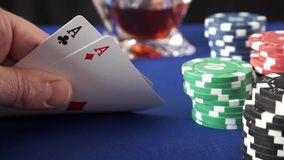 Stack of chips and two aces. On blue felt stock footage