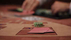 Stack of chips and two aces. POKER: The player's hand opens and looks his cards on a table stock video footage