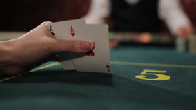 Stack of chips and two aces. POKER: The player's hand opens and looks his cards on a table stock video