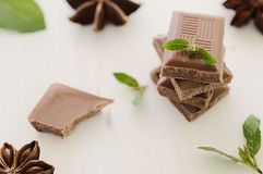 Stack of chocolate bar pieces with mint on  white. Stack of chocolate bar pieces with mint on  top against white wood background. Selective focus Stock Photo