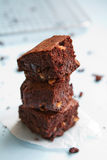 Stack of chocolate brownies on pastel blue background stock images