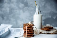 Stack of chocolate chip cookies on blue napkin with bottle of milk on light gray background. Selective focus. Copy space royalty free stock photos