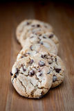 Stack of chocolate chip cookies on wooden table. Shallow DOF. Close up of stacked chocolate chip cookies on wooden background Royalty Free Stock Images