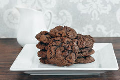 A stack of chocolate, chocolate chip cookies on a white plate. Stock Images