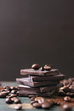 Stack of chocolate chunks with coffee beans on a wooden background Stock Image