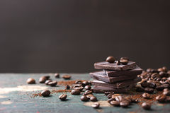 Stack of chocolate chunks with coffee beans on a wooden background Royalty Free Stock Images