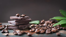 Stack of chocolate chunks with coffee beans on a wooden background Stock Images