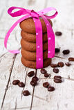 Stack of chocolate cookies tied with pink ribbon and coffee bean Stock Photos