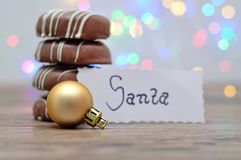 A stack of chocolate covered biscuits and a golden babble with a note for Santa. With out of focus lights stock image