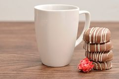 A stack of chocolate covered biscuits with a rose and mug. A stack of chocolate covered biscuits with an artificial rose and a white mug royalty free stock image
