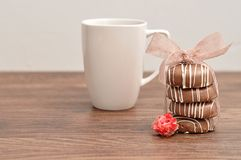 A stack of chocolate covered biscuits tied with a pink ribbon. An artificial rose and a white mug stock photos