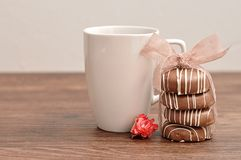 A stack of chocolate covered biscuits tied with a pink ribbon. An artificial rose and a white mug stock photography
