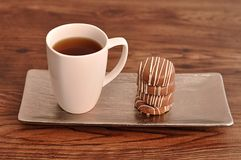 A stack of chocolate covered biscuits tied and a white mug. On a table stock photos