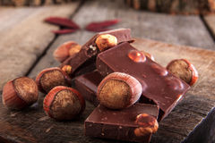A stack of chocolate with hazelnuts on wooden table Royalty Free Stock Photo