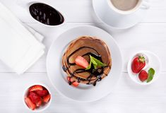 Stack of chocolate pancakes with chocolate topping and strawberries. Top view royalty free stock photography