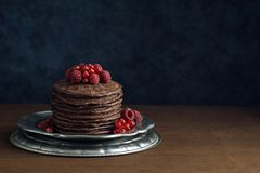 Stack of Chocolate Pancakes with Fresh Berries. A tall stack of dark chocolate pancakes topped with fresh raspberries and red currants on a metal dish. The Royalty Free Stock Photo