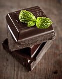 Stack of chocolate pieces. With a leaf of mint on wooden background Stock Photos