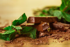 Stack of chocolate pieces with a leaf of mint on wooden background Royalty Free Stock Photo