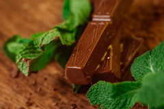 Stack of chocolate pieces with a leaf of mint on wooden background Stock Photos
