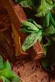Stack of chocolate pieces with a leaf of mint on wooden background Stock Images