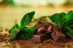 Stack of chocolate pieces with a leaf of mint on wooden background Stock Image