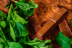 Stack of chocolate pieces with a leaf of mint on wooden background Stock Photo