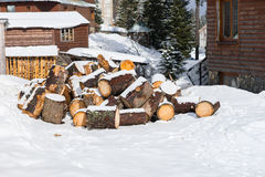 Stack of chopped fire woods on a snow. Near old wooden cottages Royalty Free Stock Photo