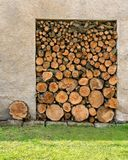 Stack of chopped firewood. Heap of wood logs ready for winter. Stack of chopped firewood. A pile of woods in the house storage. Raw barked wood logs in a Stock Images