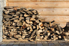 Stack of chopped logs. With wooden building in background Royalty Free Stock Image
