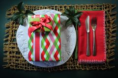 Stack of Christmas gifts on a white plate with holly and red napkins. Horizontal aspect royalty free stock photos