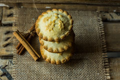 Stack of Christmas mince pies on sackcloth on a vintage wood box, with cinnamon sticks, top view, flat lay,retro royalty free stock images