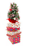 Stack of Christmas present boxes and Christmas tree Royalty Free Stock Photos