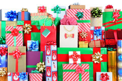 Stack of Christmas Presents. Close up of a large stack of wrapped Christmas presents of varying sizes and shapes with white space at the top. Vertical format stock photos