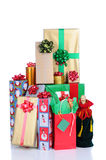 Stack of Christmas Presents. Close up of a large stack of wrapped Christmas presents of varying sizes and shapes over white background. Vertical format with royalty free stock photo